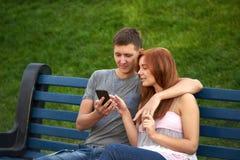Coppie che guardano le foto sul vostro telefono Fotografia Stock