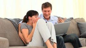 Coppie che guardano un video sul computer portatile archivi video