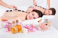 Coppie che hanno un massaggio di pietra Immagine Stock