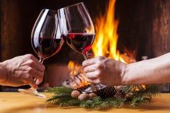 Coppie che incoraggiano con la decorazione di natale del vino rosso Immagine Stock Libera da Diritti