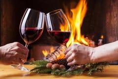 Coppie che incoraggiano con la decorazione di natale del vino rosso Fotografia Stock Libera da Diritti