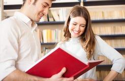 Coppie che leggono un libro in una biblioteca Fotografie Stock