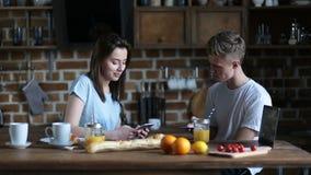 Coppie che mangiano prima colazione mentre per mezzo dei telefoni cellulari stock footage