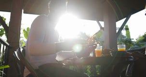 Coppie che mangiano prima colazione sulla comunicazione del terrazzo, dell'uomo e della donna di estate mentre godendo del pasto  video d archivio