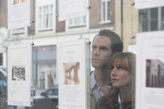 Coppie che osservano attraverso la finestra gli agenti immobiliari Immagine Stock Libera da Diritti