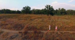 Coppie che pareggiano attraverso il pascolo su un sentiero per pedoni stock footage