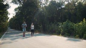 Coppie che pareggiano lungo la strada asfaltata in foresta video d archivio