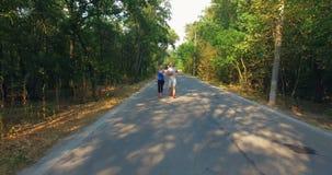 Coppie che pareggiano lungo la strada in foresta video d archivio