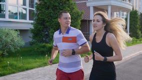Coppie che pareggiano nella via Funzionando nella città Uomo e donna che fanno gli sport video d archivio