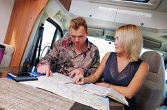 Coppie che parlano dell'itinerario futuro di pianificazione di avventura che esamina mappa fotografie stock libere da diritti
