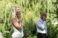 Coppie che parlano sul cellulare o sullo Smart Phone L'uomo e la donna parlano con il telefono I giovani utilizzano il cellulare  fotografia stock
