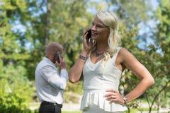 Coppie che parlano sul cellulare o sullo Smart Phone L'uomo e la donna parlano con il telefono I giovani utilizzano il cellulare  immagine stock libera da diritti