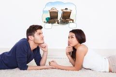 Coppie che pensano alla vacanza di spesa sulla spiaggia Fotografia Stock Libera da Diritti
