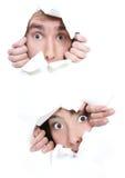 Coppie che pigolano attraverso il foro in documento Fotografie Stock
