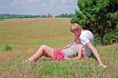 Coppie che pongono sull'erba vicino al prato Fotografia Stock Libera da Diritti