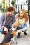 Coppie che prendono cane per la passeggiata sulla via della città Fotografia Stock Libera da Diritti