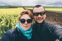 Coppie che prendono selfie nel giacimento del canola fotografia stock libera da diritti