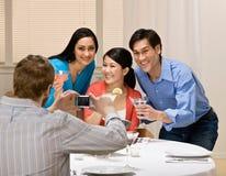 Coppie che propongono per la fotografia al partito di pranzo Fotografia Stock