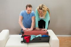 Coppie che provano a chiudere bagagli Fotografie Stock Libere da Diritti