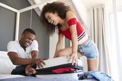 Coppie che provano a chiudere la valigia piena di festa in camera da letto fotografia stock libera da diritti