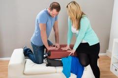 Coppie che provano a chiudere valigia a casa Immagine Stock