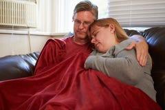 Coppie che provano a tenere coperta di sotto calda a casa Fotografie Stock Libere da Diritti