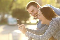 Coppie che ridono con il contenuto di media in un telefono Immagine Stock Libera da Diritti