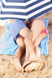 Coppie che riparano a partire da Sun sotto l'ombrello di spiaggia Fotografia Stock