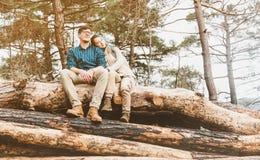 Coppie che riposano sui tronchi di albero immagini stock