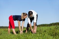 Coppie che riscaldano per l'esercitazione in estate Fotografie Stock Libere da Diritti