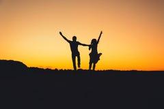 Coppie che saltano allegro al tramonto di estate Fotografia Stock Libera da Diritti
