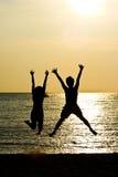 Coppie che saltano nella siluetta Fotografia Stock Libera da Diritti