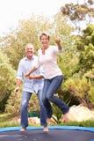 Coppie che saltano sul trampolino in giardino Fotografia Stock Libera da Diritti