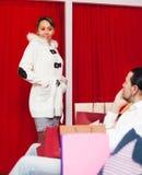 Coppie che scelgono cappotto al deposito di modo Fotografie Stock Libere da Diritti