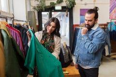 Coppie che scelgono i vestiti al negozio di vestiti d'annata Fotografia Stock