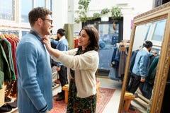 Coppie che scelgono i vestiti al negozio di vestiti d'annata fotografia stock libera da diritti