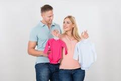 Coppie che se esaminano mentre tenendo l'abbigliamento del bambino fotografia stock libera da diritti