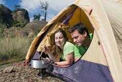 Coppie che si accampano in tenda, cucinante Immagine Stock