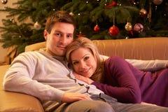 Coppie che si distendono davanti all'albero di Natale Fotografie Stock