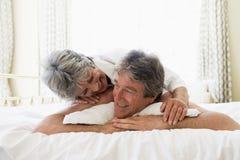 Coppie che si distendono nella camera da letto e nel sorridere Fotografia Stock Libera da Diritti