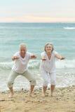 Coppie che si esercitano sulla spiaggia Fotografie Stock