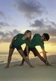 Coppie che si esercitano sulla spiaggia all'alba Fotografia Stock Libera da Diritti
