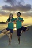 Coppie che si esercitano sulla spiaggia all'alba Fotografia Stock