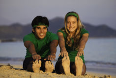 Coppie che si esercitano sulla spiaggia all'alba Immagini Stock Libere da Diritti