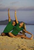 Coppie che si esercitano sulla spiaggia all'alba Fotografie Stock Libere da Diritti
