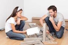 Coppie che si muovono in mobilia di montaggio del letto Immagine Stock