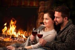 Coppie che si rilassano con il bicchiere di vino al camino Fotografie Stock Libere da Diritti