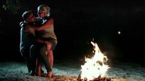 Coppie che si rilassano vicino al fuoco di accampamento alla notte archivi video
