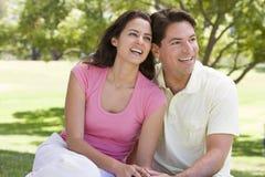 Coppie che si siedono all'aperto sorridere Immagine Stock Libera da Diritti