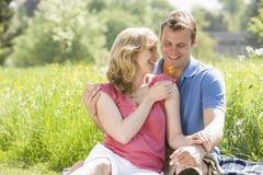 Coppie che si siedono all'aperto tenendo sorridere del fiore Fotografie Stock Libere da Diritti